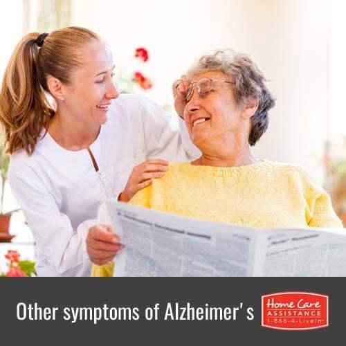 Caregiver Helping Senior Woman Read Newspaper